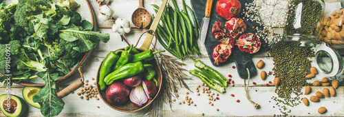 Photo sur Toile Magasin alimentation Winter vegetarian, vegan food cooking ingredients. Flat-lay of vegetables, fruit, beans, cereals, kitchen utencil, dried flowers, olive oil over white wooden background, top view. Clean eating food