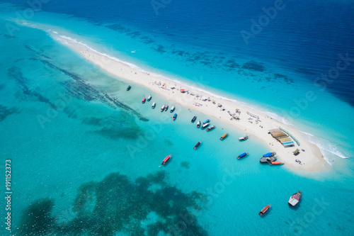 Aerial view of beautiful sand tropical island with white sand beach and tourists, Zanzibar