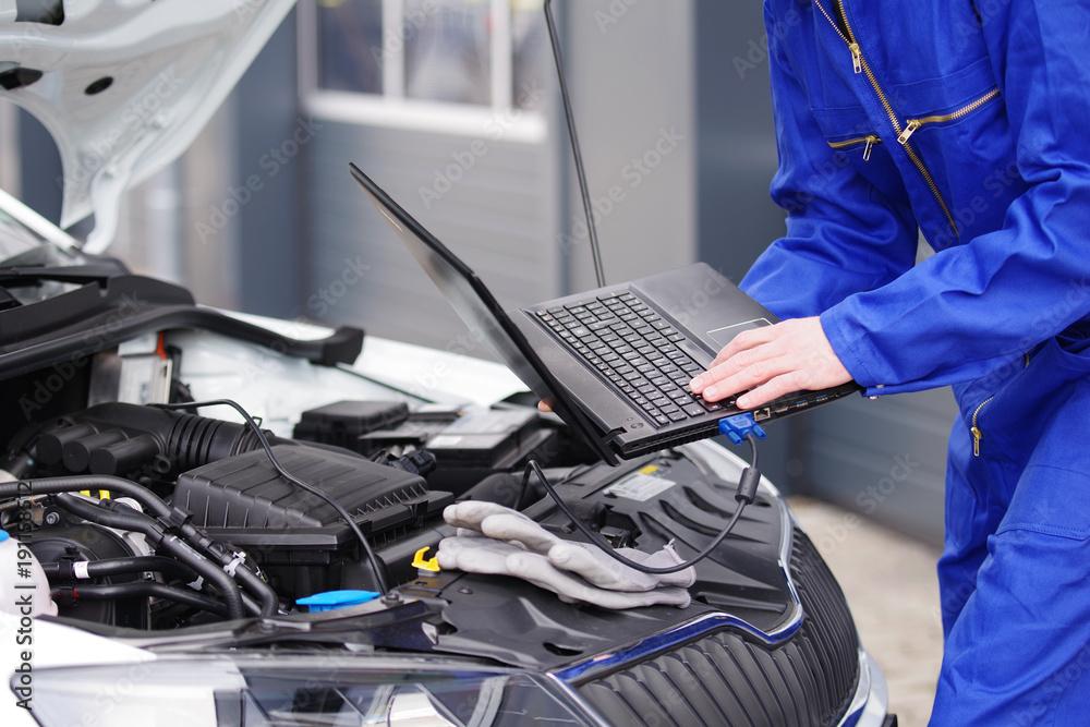 Fototapeta Mechaniker arbeitet mit einem Laptop an einem Auto, Motorsteuerung
