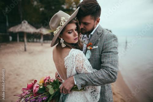 Fotomural beautiful bride and groom in boho style hugging on beach