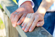 Newlywed couple's hands on wood background with wedding rings