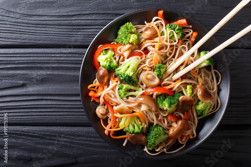 fried soba noodles with mushrooms, broccoli, carrots, peppers closeup on a plate. horizontal top view