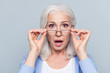 canvas print picture - Close up portrait of stylish, aged, charming, surprised, shocked woman holding eyelets peek out glasses with wide open eyes and mouth over grey background