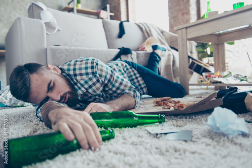 Fototapeta Sick drunk dreamy bearded guy clothed in checkered shirt and denim jeans is slee