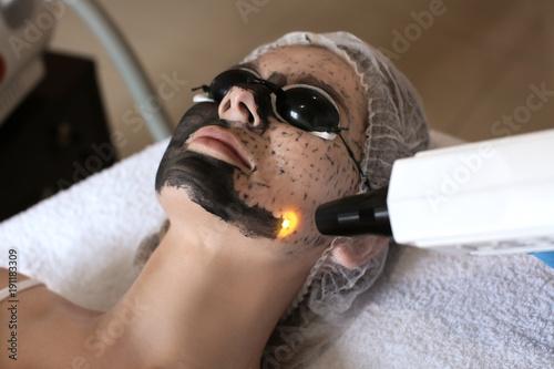 Valokuva  Young woman undergoing carbon peeling procedure in salon