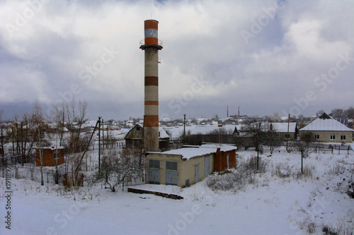 Staande foto Industrial geb. High boiler tube of the destroyed and abandoned building of the bakery on the background of winter trees and a blue cold winter sky. The structure of the times of the USSR. Ruin and vandalism.