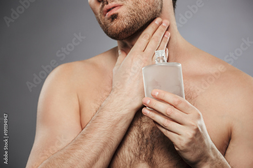 Portrait cropped of handsome half-naked man putting perfume on his neck, isolate Canvas Print