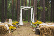 canvas print picture - Beautifully decorated place in old autumn wood for wedding ceremony. Rustic style of elements of decor. Unusual seats made with straw. Horizontal color photography.