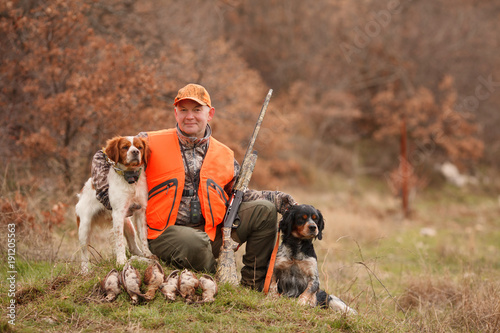 Valokuva  hunter with two hunting dogs, a gun and a woodcock after a hunt