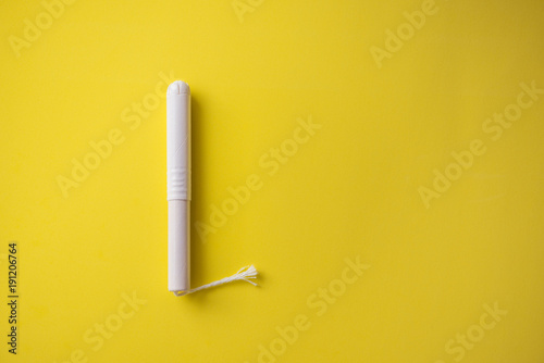 Feminine tampon with paper applicator on yellow background Wallpaper Mural