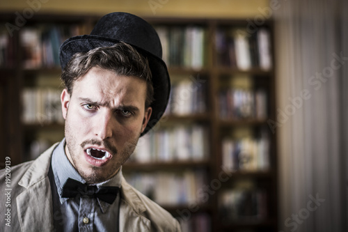 Spoed Foto op Canvas Muziekwinkel Close up Young Handsome White Vampire with Black Top Hat Inside the Mini Library
