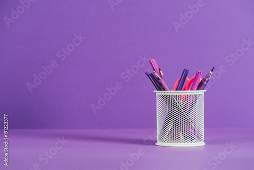 Obraz na plátně  pen holder with various pens and pencils on purple surface