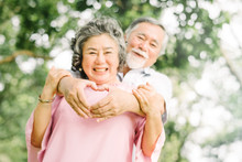 Happy Smile Senior Asian Couple Enjoying Quality Time At The Park And Making Heart Sign. Focus On Hand