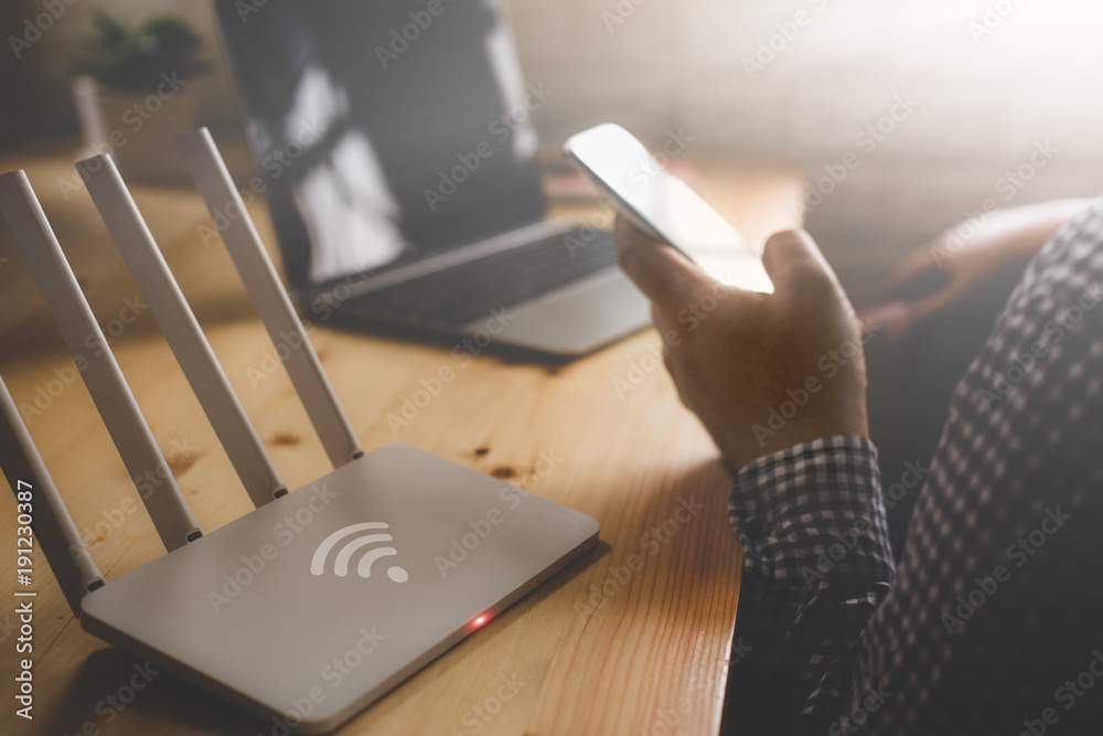 Fototapeta closeup of a wireless router and a man using smartphone on living room at home ofiice