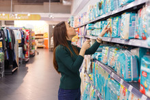 Young Woman Looking At Diapers In A Supermarket.
