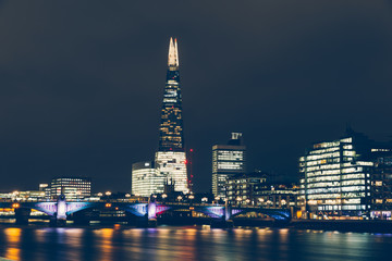 London skyline at night with shard building and reflections on River Thames