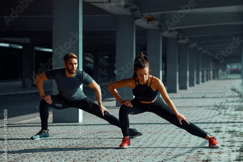 Fototapeta Young couple stretching legs in urban environment
