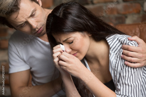 Young man comforting crying sad woman, caring friend consoling upset girl in tea Fototapeta