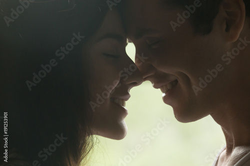 Loving man and woman getting closer to kiss each other, happy young sensual coup Wallpaper Mural