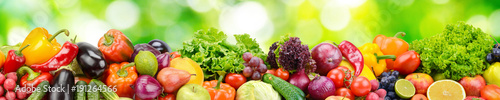 Panorama of fresh vegetables and fruits on blurred background of green leaves. - 191264566