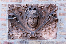 Stone Face Decoration On A Brick Building Wall
