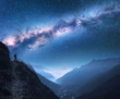 Leinwanddruck Bild - Space with Milky Way, girl and mountains. Silhouette of standing woman on the mountain peak, mountains and starry sky at night in Nepal. Sky with stars. Trekking. Night landscape with bright milky way