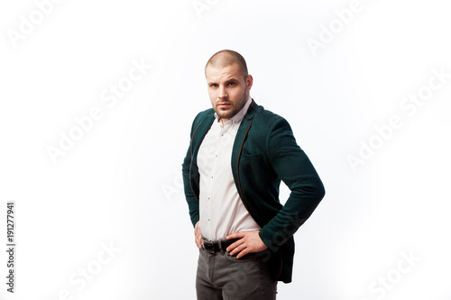 Fotografie, Obraz  A young bald man in a white shirt, green suit confidently looks at the camera an
