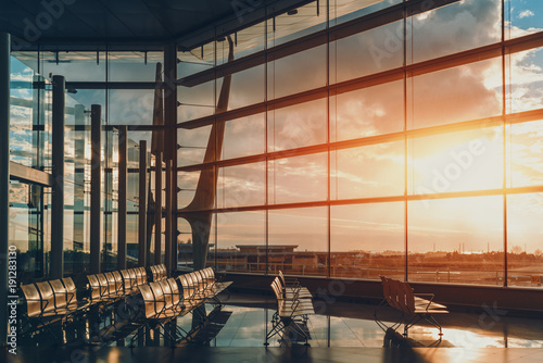 Photo sur Toile Aeroport Abstract huge glass and metal interior of shopping mall or airport terminal, or railway station depot with multiple rows of empty seats, giant window facade and glass wall with steel beams