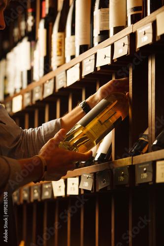 Obraz na plátně Expert in winemaking choose elite white wine in cellar.
