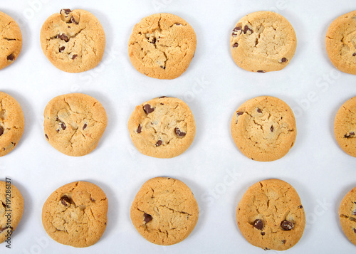 Tuinposter Koekjes flat view from above fresh baked soft and chewy chocolate chip cookies on a baking tray covered in parchment paper. A popular homemade treat for adults and children alike.