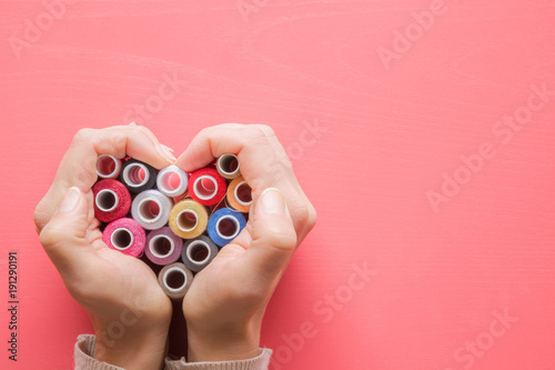 Fotomural  Colorful spools of threads in hands heart shape on the pastel pink background