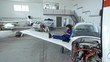 Tilt down of young female aircraft mechanic sitting on wing of jet airplane in hangar and texting on smartphone while having a break