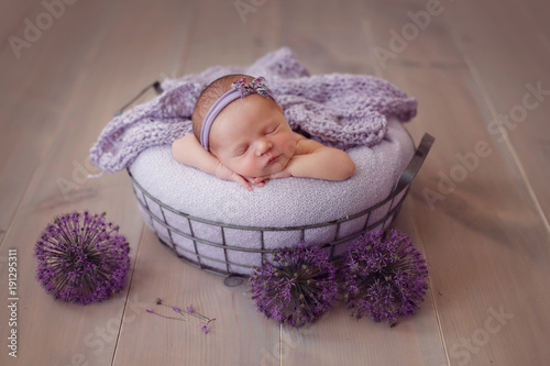 newborn baby sleeping in a basket, on a wooden background and purple onions