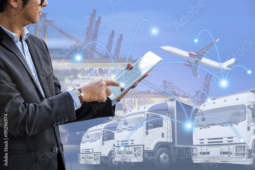 Fotografia, Obraz  Double exposure businessman touching digital tablet for analysis and checking stock at logistics port, Transportation trading business concept