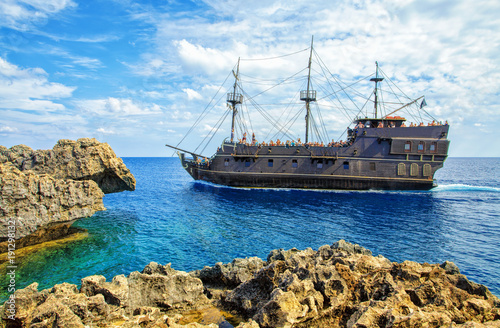 Foto op Canvas Cyprus The bridge of love or love bridge. Pirate ship sailing near famous Bridge of Love near Ayia Napa, Cyprus.