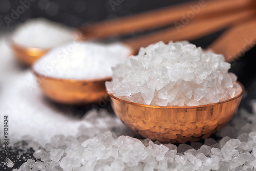 Three copper spoons with coarse salt close up. Fotobehang