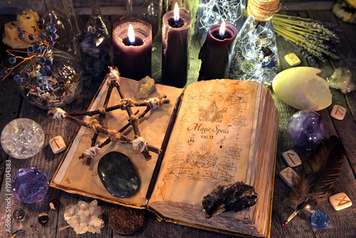 Old witch book with pentagram, black candles, crystals and ritual objects. Occult, esoteric, divination and wicca concept. No foreign text, all symbols on pages are fantasy, imaginary ones