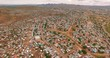 A bird's-eye view taken over a city with ruined houses in Namibia, Africa. The poor people live in these slums. Houses were taken off in a sunny summer in Africa with the help of a drone 4K