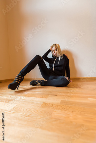 Fototapety, obrazy: A beautiful young woman sitting on the floor and wearing black clothes.