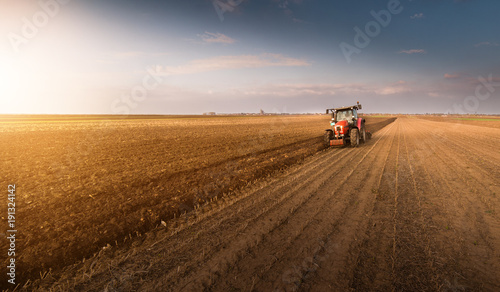 Foto  Tractor plowing fields -preparing land for sowing in autumn