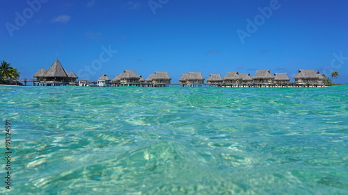 Tropical resort with thatched bungalows in the lagoon seen from sea surface, Tikehau atoll, Tuamotus, French Polynesia, Pacific ocean, Oceania