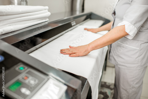 Fotografie, Obraz  Ironing bedclothes with professional ironing machine in the laundry