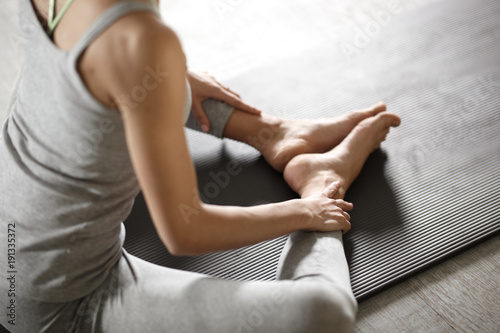 Foto op Canvas Ontspanning Relaxed young sportswoman doing yoga and meditating in studio