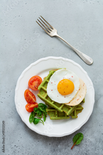 Fried egg with cheese, tomatoes, chard, and waffle with spinach on white ceramic plate on light gray concrete background. Sandwich for breakfast. Selective focus. Top view. Copy space.