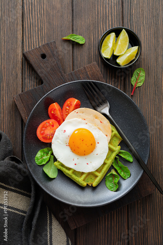 Fried egg with cheese, tomatoes, chard, and waffle with spinach on black ceramic plate on brown old wooden background. Sandwich for breakfast. Selective focus. Top view. Copy space.