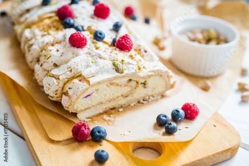Fényképezés Homemade Meringue Almond Roll with Berries, Pistachios, Cream and Lemon Curd
