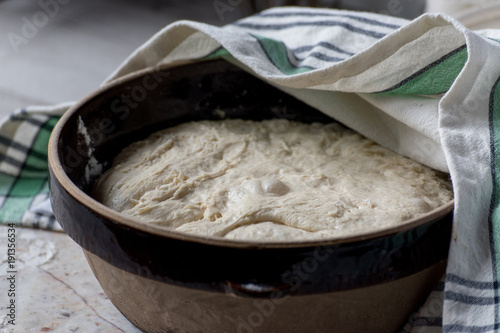 Fotografie, Obraz  dough rising in large brown bowl covered with tea towel