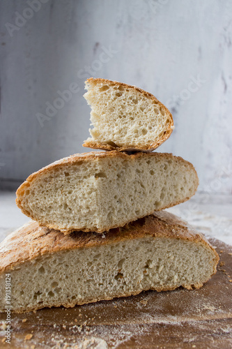 Foto op Canvas Brood stacked slices of baked bread on wooden platter sitting on marble table