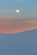 A Super Moon Rising Over Beautiful White Sand Dunes At Sunset