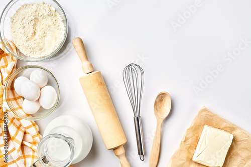 Preparation of the dough. A measurement of the amount of ingredients in the recipe. Ingredients for the dough: flour, eggs, rolling pin, whisk, milk, butter, cream. Top view, space for text